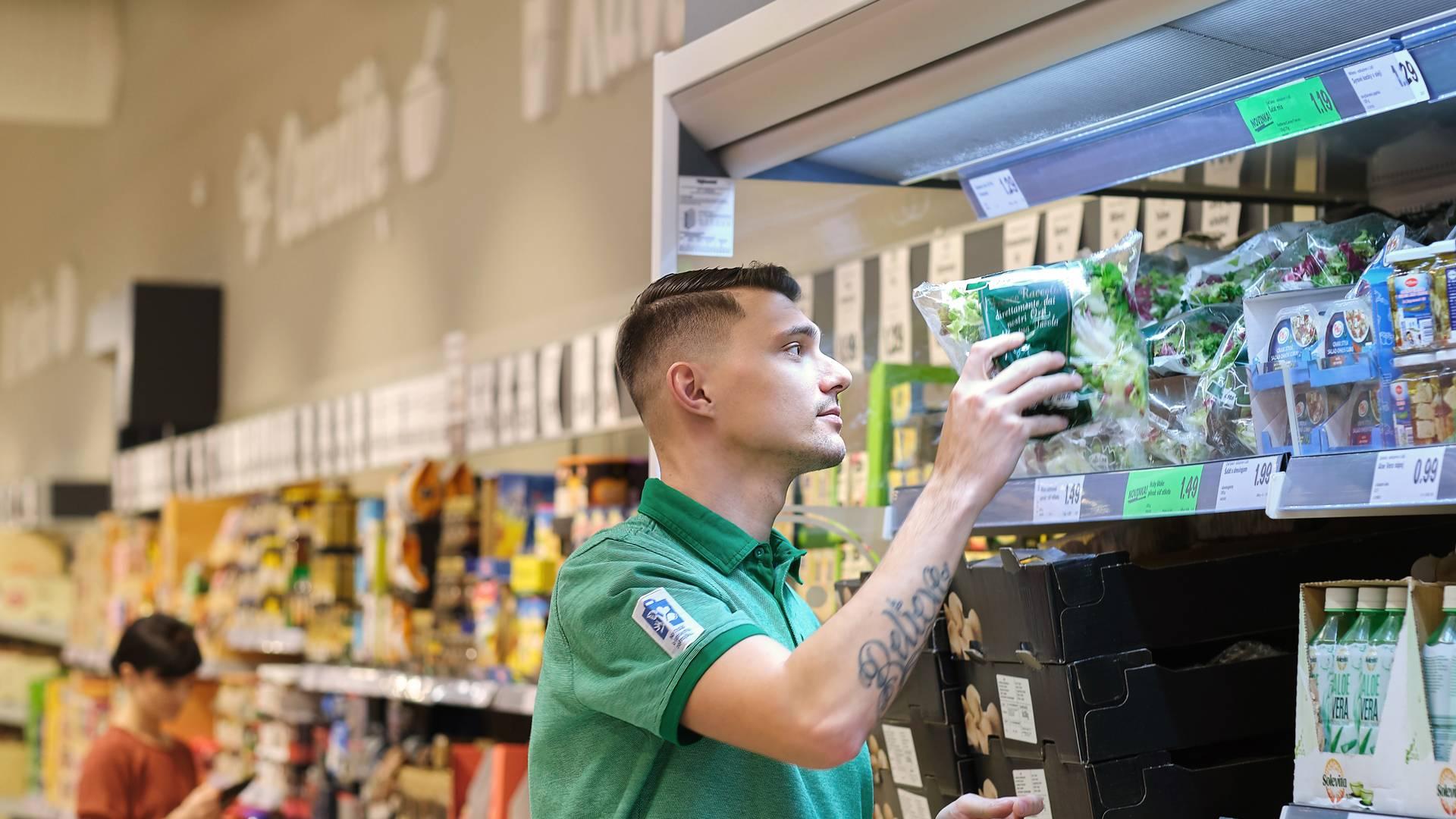 Asistent manažéra predajne upravuje šalát